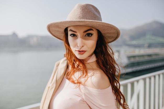 Linda mulher ruiva de cabelos compridos com expressão facial séria em pé no oceano