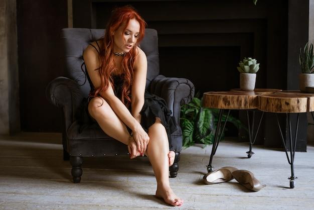 Linda mulher ruiva de vestido preto sentada na cadeira tirou os sapatos conceito de desconfortável ...
