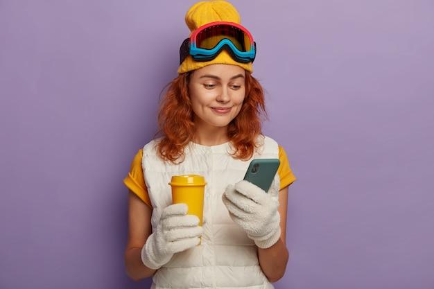 Linda mulher ruiva descansa depois dos esportes de inverno, verifica a caixa de e-mail, segura uma xícara de café para viagem, usa óculos de snowboard, isolada sobre a parede roxa