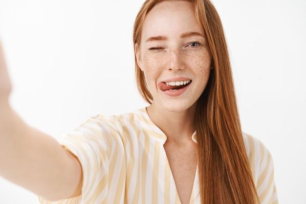 Linda mulher ruiva feminina com sardas fofas piscando para fora da língua, glamour e tirando selfie com alegria