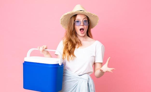 Linda mulher ruiva maravilhada, chocada e atônita com uma surpresa inacreditável e segurando uma geladeira portátil de piquenique