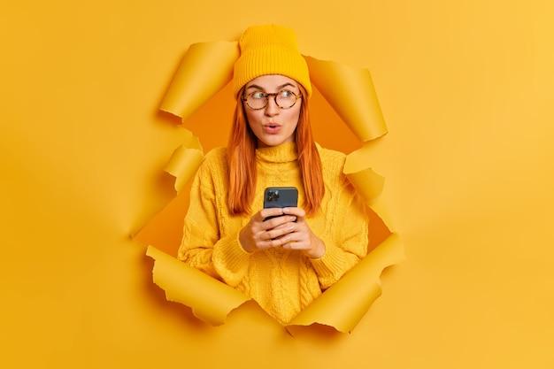 Linda mulher ruiva milenar com um elegante chapéu amarelo e macacão usa celular moderno para comunicação online, olha maravilhada.