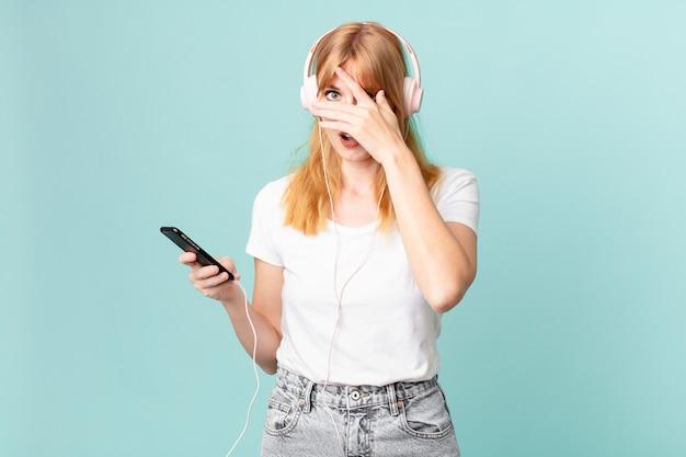 Linda mulher ruiva parecendo chocada, assustada ou apavorada, cobrindo o rosto com a mão e ouvindo música com fones de ouvido