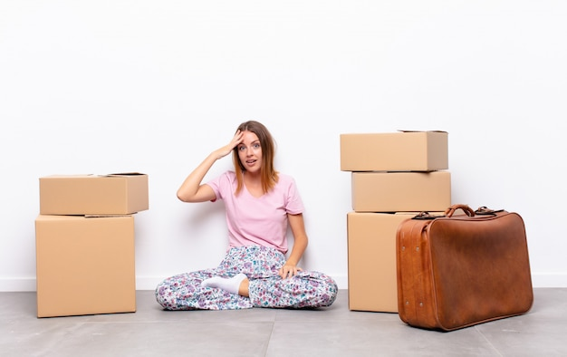Linda mulher ruiva parecendo feliz, atônita e surpresa, sorrindo e percebendo uma boa notícia incrível em um novo lar