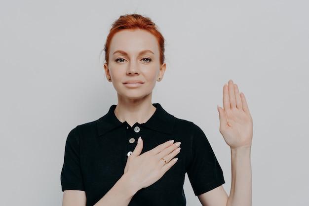 Linda mulher ruiva patriótica xingando com a mão no peito e a palma da mão aberta