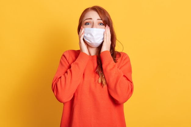 Linda mulher ruiva se agarra à cabeça e fica chocada com a propagação do vírus corona. menina ruiva com máscara protetora no espaço amarelo