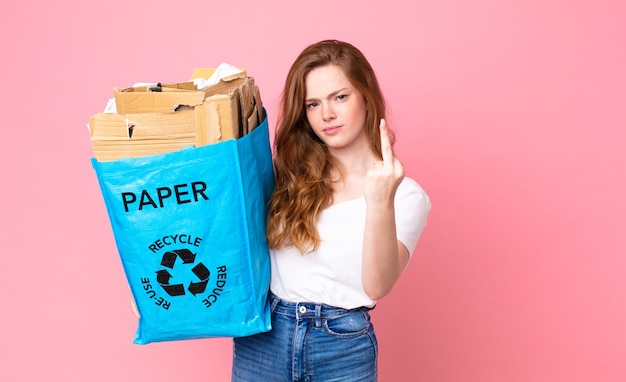 Linda mulher ruiva se sentindo irritada, irritada, rebelde e agressiva segurando um saco de papel reciclado