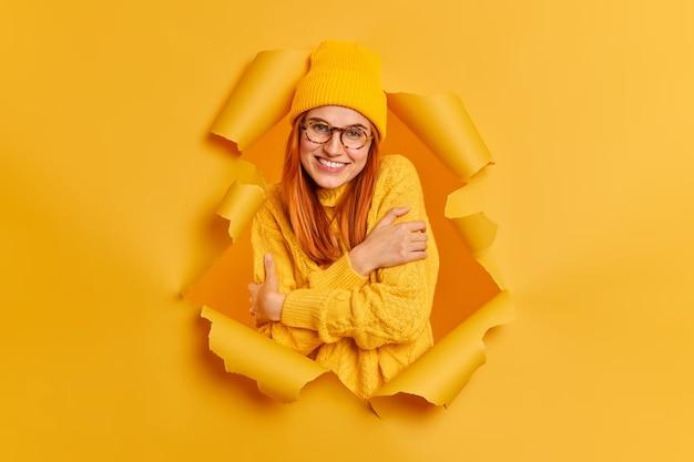 Linda mulher ruiva sorridente se abraça, sente conforto, veste um suéter de malha quente parece feliz.