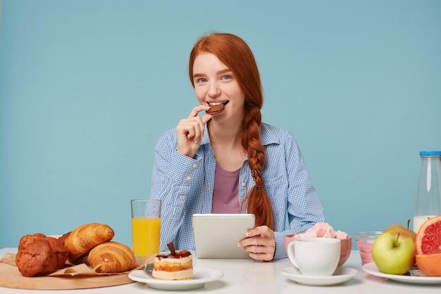 Linda mulher ruiva sorridente tomando café da manhã lendo notícias em seu tablet olhando para frente e comendo biscoito de chocolate