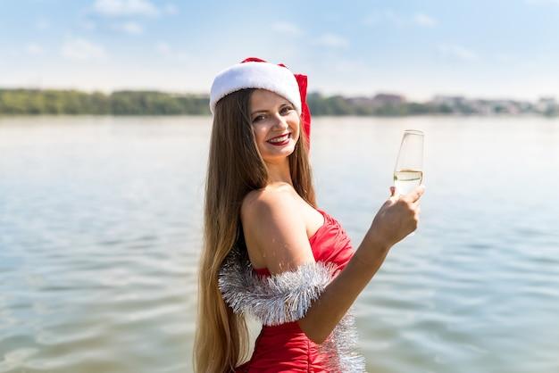 Linda mulher santa posando na água com champanhe