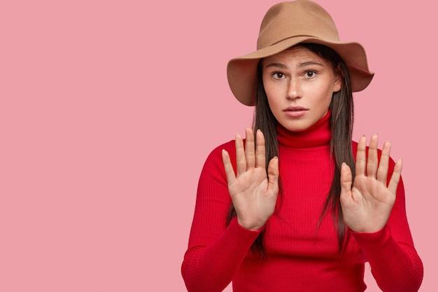 Linda mulher sardenta com aparência específica faz gesto de pare, projeta as mãos sobre o peito, mostra palmas