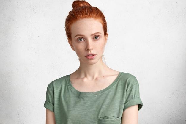 Linda mulher sardenta com nó no cabelo ruivo, vestida casualmente, escuta atentamente palestra, isolada sobre o branco