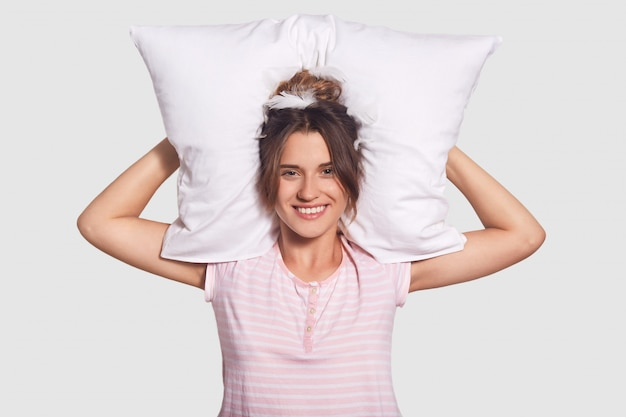 Linda mulher satisfeita com um sorriso encantador, mantém o travesseiro atrás da cabeça