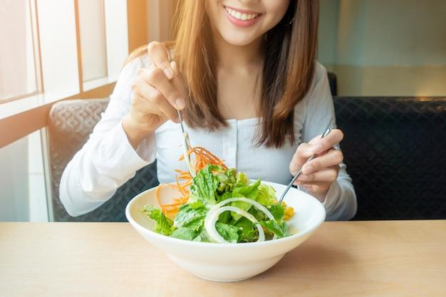 Linda mulher saudável está segurando salada de legumes