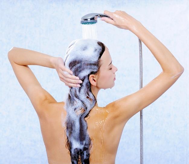Linda mulher se afastando e lavando seus longos cabelos