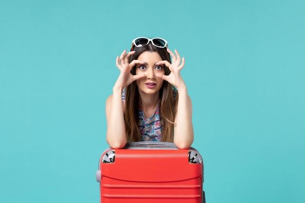 Linda mulher se preparando para a viagem com sua grande bolsa vermelha mostrando os olhos no espaço azul de frente