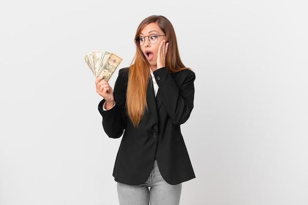 Linda mulher se sentindo feliz, animada e surpresa. conceito de negócios e dólares