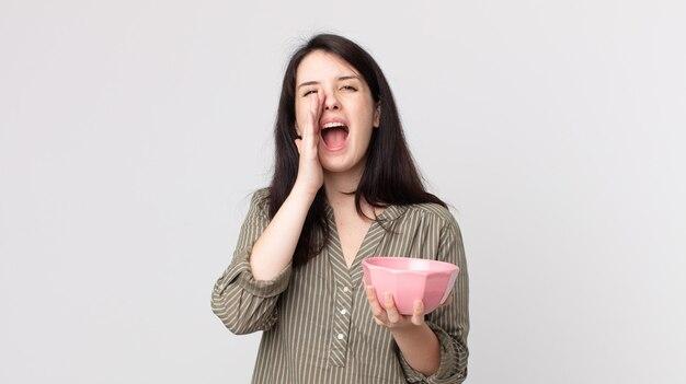 Linda mulher se sentindo feliz, dando um grande grito com as mãos perto da boca, segurando uma tigela de panela vazia. agente assistente com fone de ouvido