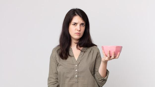 Linda mulher se sentindo triste, chateada ou com raiva e olhando para o lado segurando uma tigela de panela vazia. agente assistente com fone de ouvido