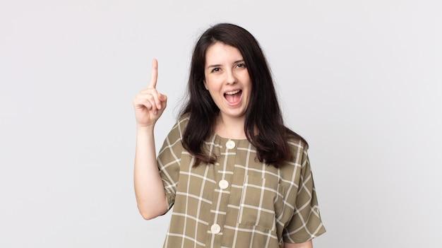Linda mulher se sentindo um gênio feliz e animado depois de realizar uma ideia, levantando o dedo alegremente, eureka!