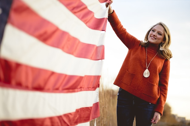 Linda mulher segurando a bandeira americana em pé perto das árvores