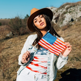 Linda mulher segurando a bandeira americana na natureza