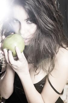 Linda mulher segurando a maçã verde e olhando de vestido preto.