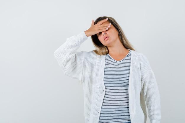 Linda mulher segurando a mão na cabeça com jaqueta, camiseta e parecendo cansada. vista frontal.