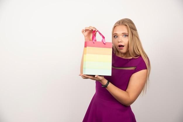 Linda mulher segurando a sacola de presente com uma expressão feliz.