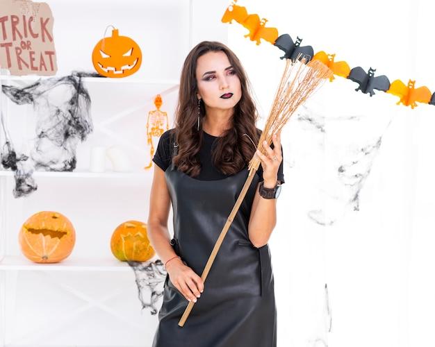 Linda mulher segurando a vassoura de halloween