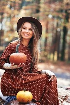 Linda mulher segurando abóboras na floresta de outono