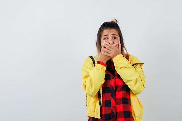 Linda mulher segurando as mãos na boca em uma camisa, jaqueta e parecendo ansiosa. vista frontal.
