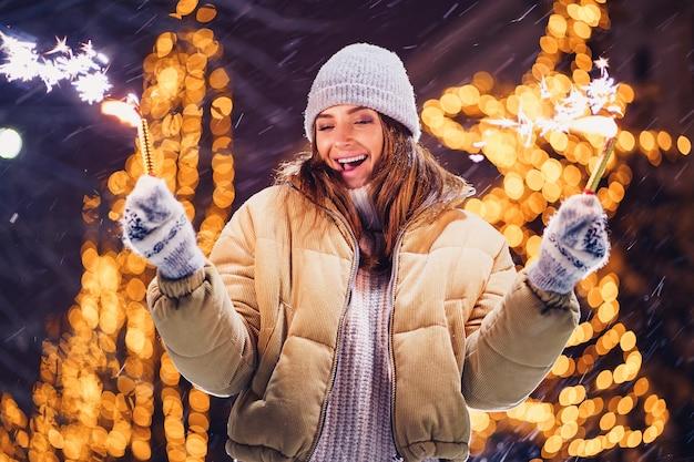 Linda mulher segurando brilhos e divirta-se ao ar livre