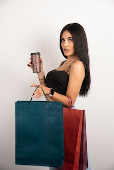 Linda mulher segurando café e sacolas de compras. foto de alta qualidade