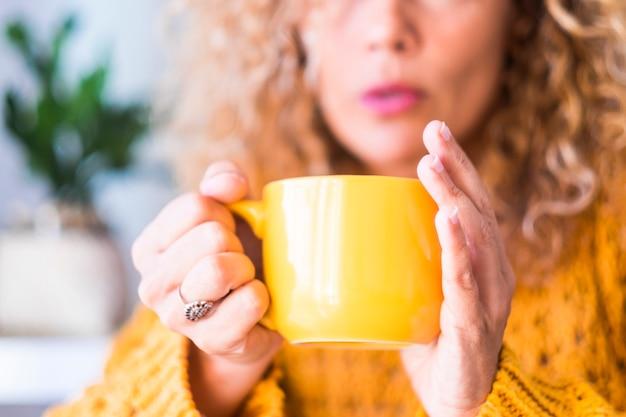 Linda mulher segurando com as duas mãos uma xícara de café ou chá em casa ou no restaurante ou bar