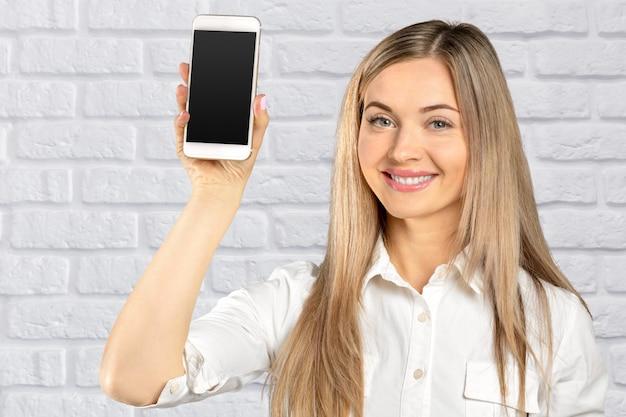 Linda mulher segurando e mostrando o celular branco com tela preta em branco