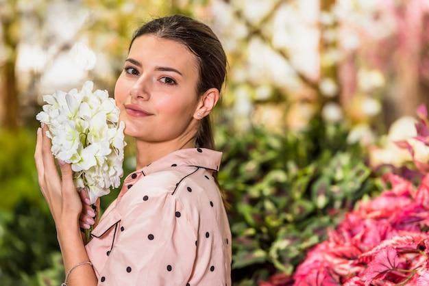 Linda mulher segurando flor branca em casa verde