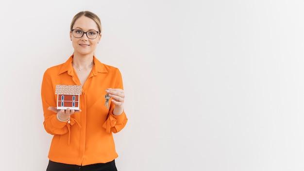 Linda mulher segurando modelo de casa e chave na frente da parede branca