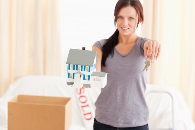 Linda mulher segurando modelo de casa e chaves