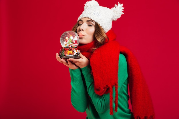 Linda mulher segurando o brinquedo de natal com os olhos fechados beijando.