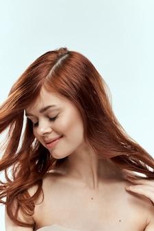 Linda mulher segurando o cabelo sorrir cosméticos estilo de vida ombros nus penteado cuidados charme luz.