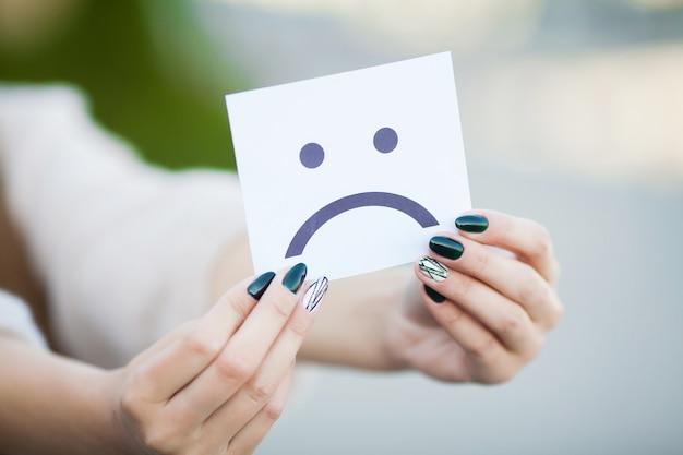 Linda mulher segurando o cartão com um sorriso triste