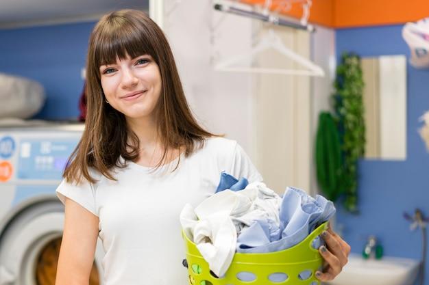 Linda mulher segurando o cesto de roupa suja