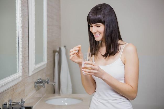 Linda mulher segurando o comprimido e copo de água no banheiro