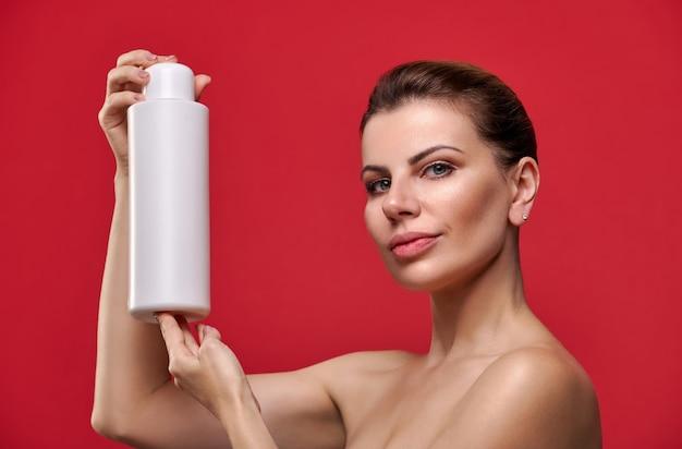Linda mulher segurando o frasco de shampoo