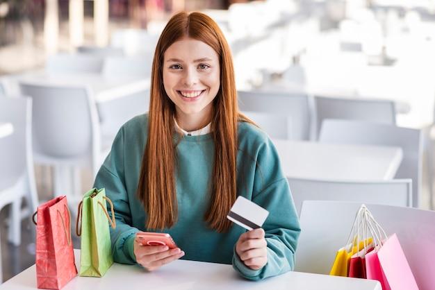 Linda mulher segurando o telefone e cartão de crédito