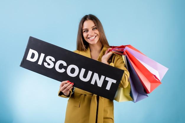 Linda mulher segurando sinal de compras preto com desconto e sacolas coloridas isoladas sobre azul
