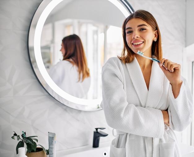 Linda mulher segurando sua escova de dente