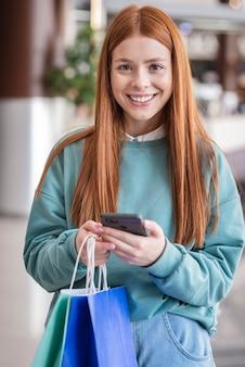 Linda mulher segurando telefone e sacos de papel