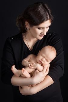 Linda mulher segurando um bebê recém-nascido nos braços. fundo preto